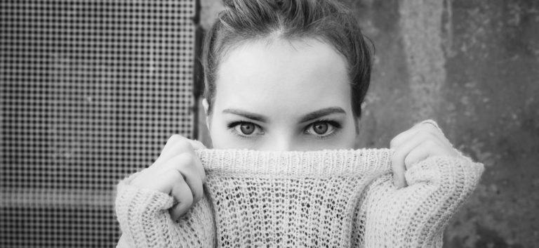 女性 顔を隠す 視線 見つめる