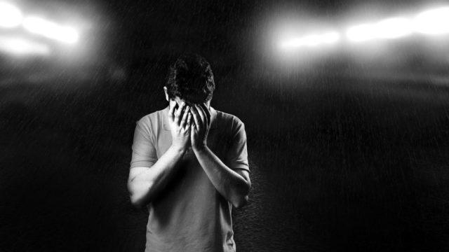 顔を覆う男性 雨 焦り 不安 悲しみ