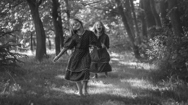 走る双子の女の子 森林 笑顔