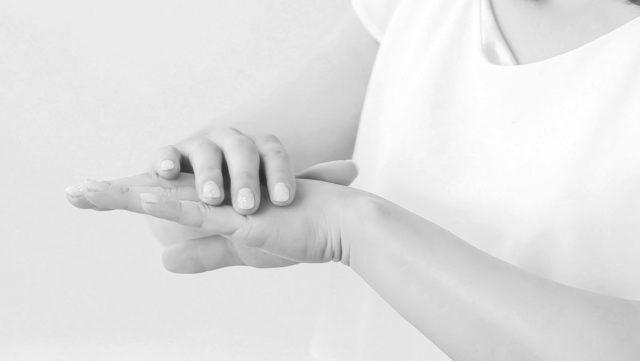 腕を触る女性