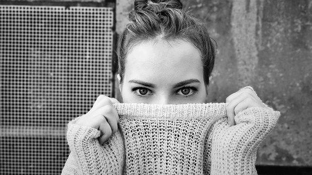 顔・口・鼻をニットで隠す女性