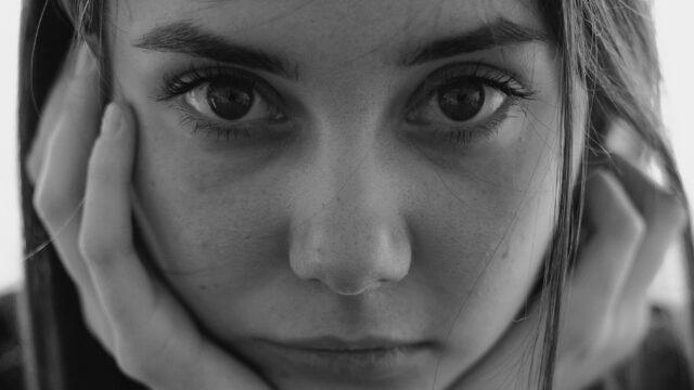 女性の両目 見つめる 頬杖